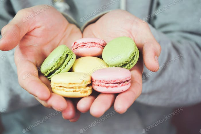 Detail of man hands holding macaroons