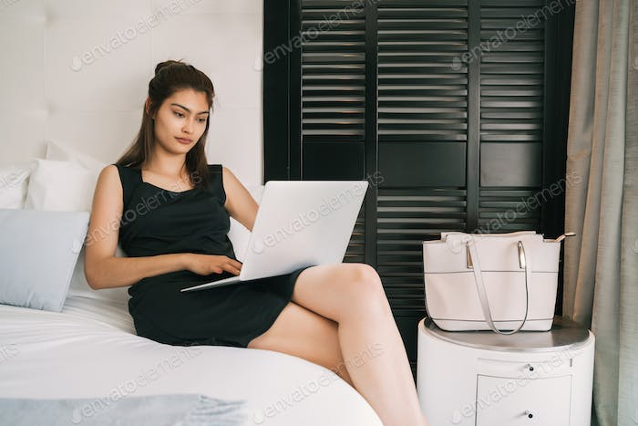 businesswoman working on her laptop at the hotel room..