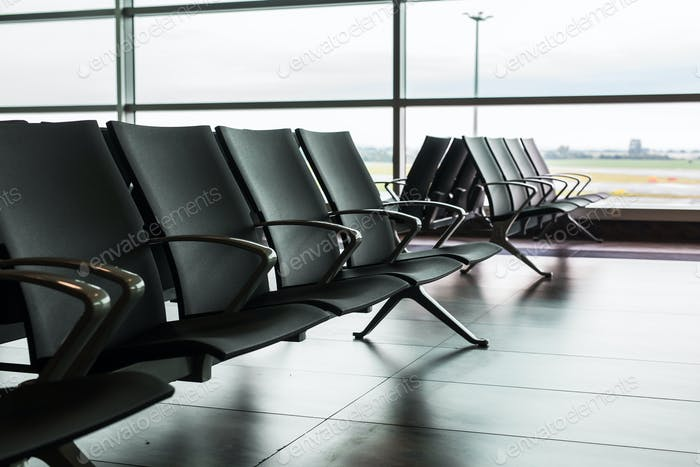 Empty airport terminal waiting area with chairs.