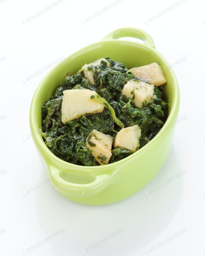 porcelain pan with spinach cooked with potatoes