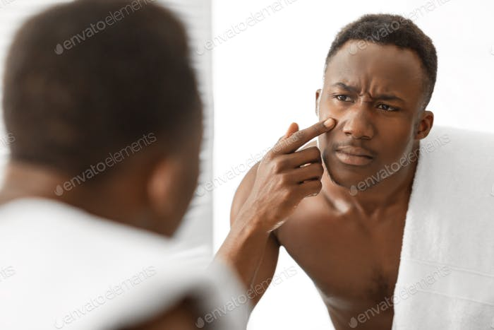African Man Touching Acne Pimple On Face Standing In Bathroom