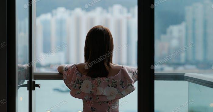 Frau gehen Balkon und genießen Sie den Blick auf die Stadt