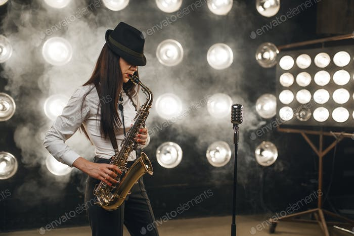 Female jazz musician in hat plays the saxophone