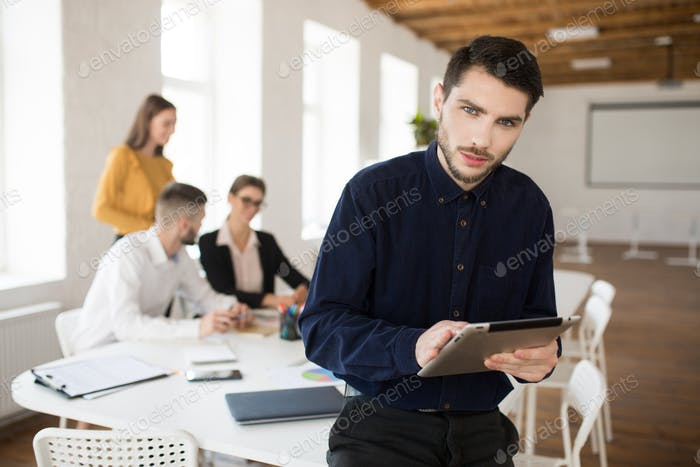 Young business man with beard in shirt thoughtfully looking in c