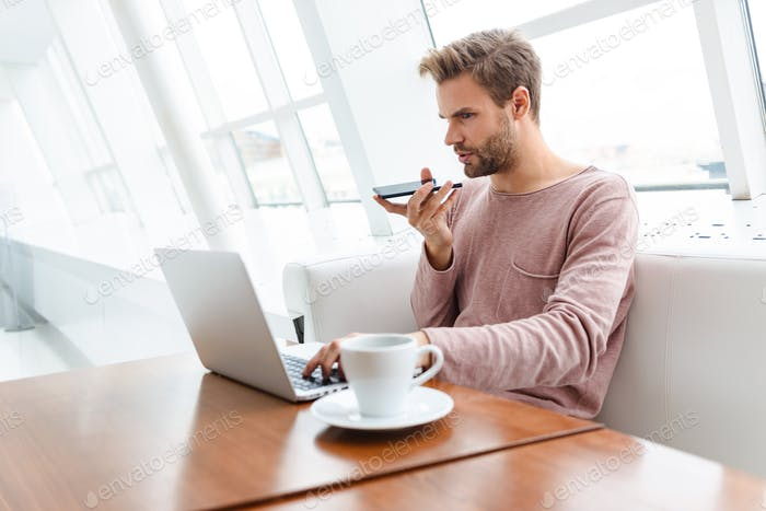 Image of young bearded man using smartphone and laptop in cafe indoors
