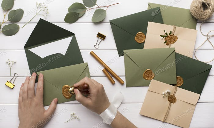 Woman preparing invitations for wedding on white wooden table