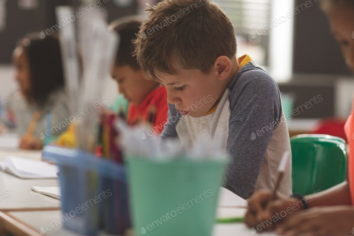 School boy writing a dictation on a notebook in a classroom