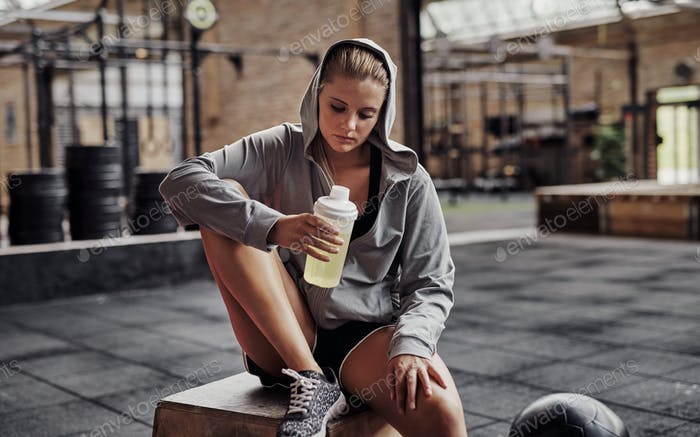 Young woman in workout clothing drinking water at the gym