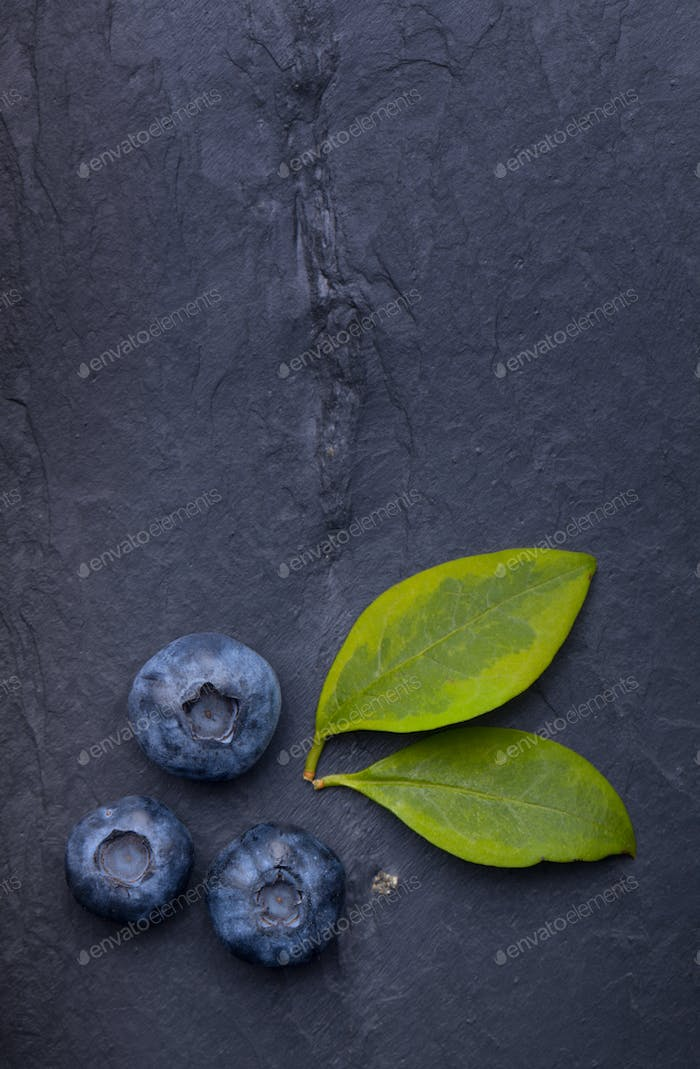 A bunch of delicious blueberries with green leaves on a dark bla