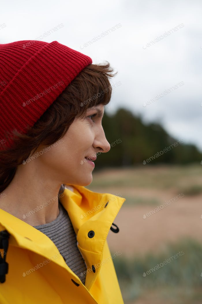 One with nature. Crop closeup portrait of mature beautiful woman in bright yellow jacket and red hat