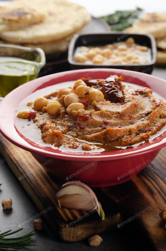 Frisch hausgemachter Hummus in Tonschale mit Olivenöl gekrönt