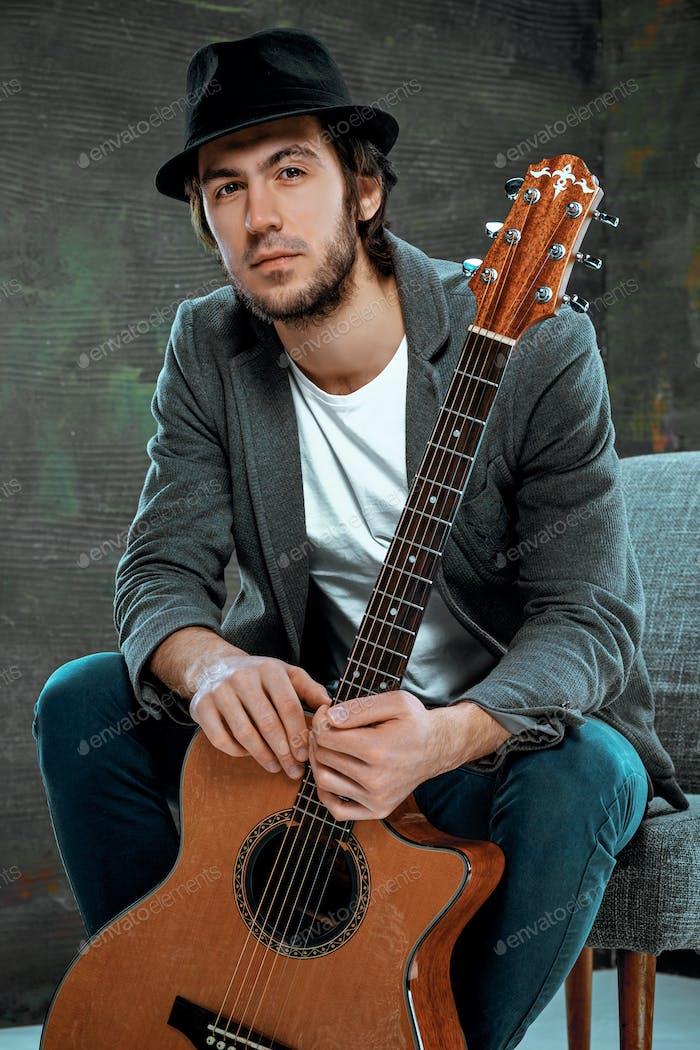 Coole Kerl sitzt mit Gitarre auf grauem Hintergrund