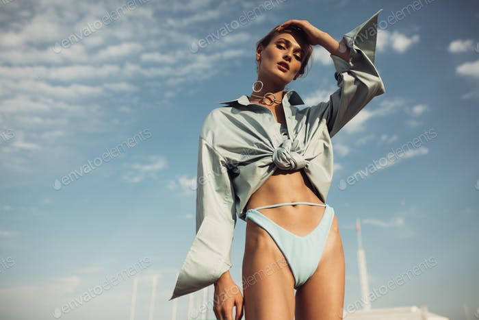 Beautiful lady in shirt and swimsuit wearing modern jewelry dreamily looking in camera over blue sky