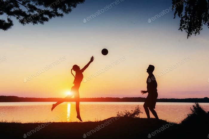 couple in play at sunset by the lake
