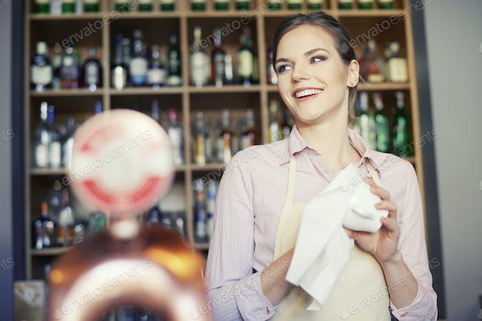 Kellnerin putzen Gläser an der Bar Theke