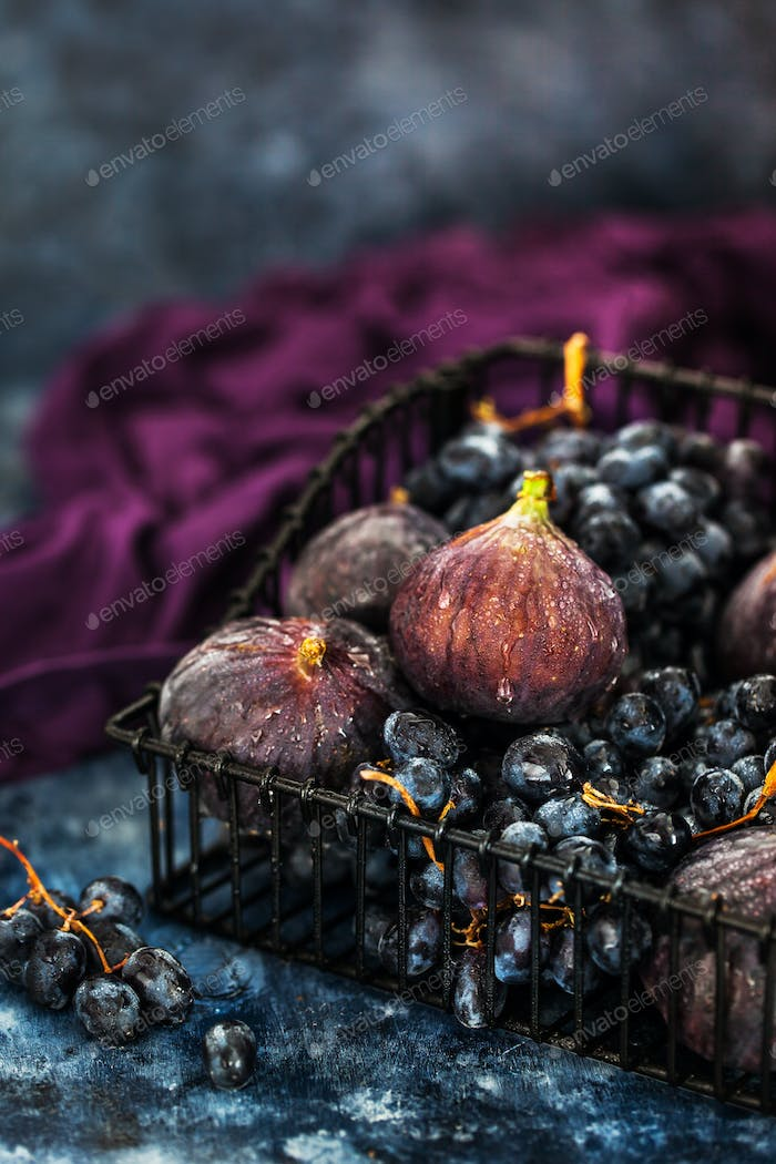 Fresh figs and purple grape in basket