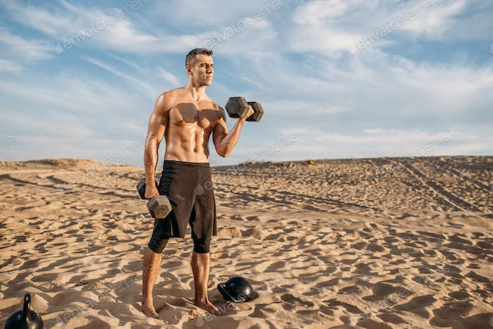 Sportsman doing exercise with weights in desert