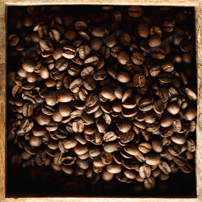 Rohe und geröstete Kaffeebohnen in Holzkiste. Zutaten für Kaffeegetränk. Food-Hintergrund