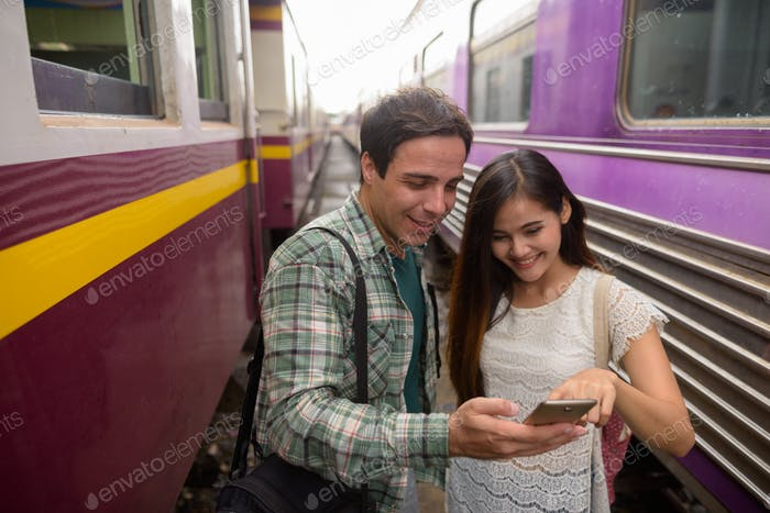 Tourist man and young Asian woman using phone at train station