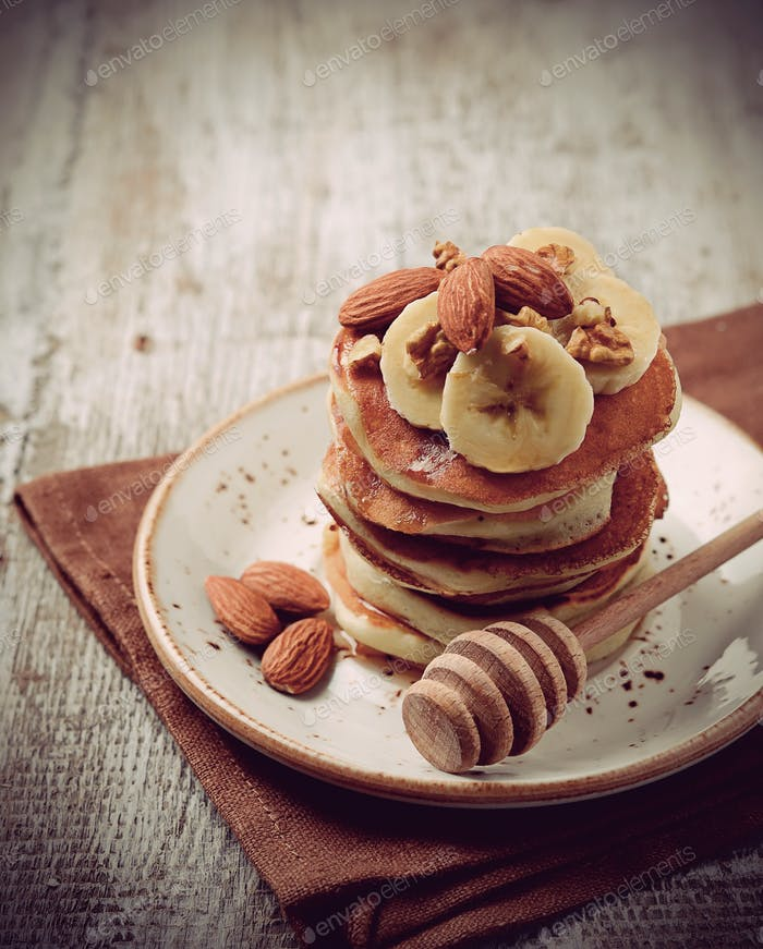 Pancakes with nuts, banana and maple syrup