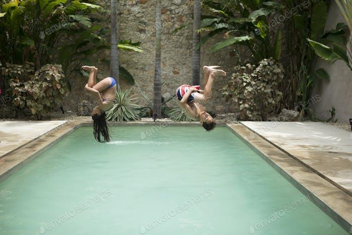 Zwei Kinder in der Luft, die rückwärts in ein Schwimmbad salzen.