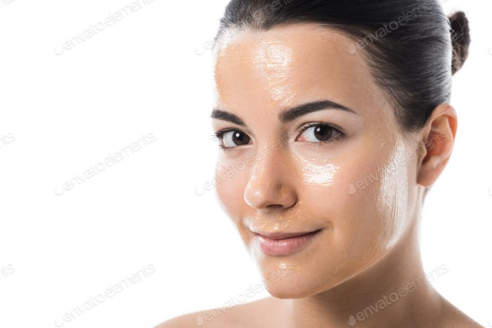 beautiful girl with honey mask looking at camera isolated on white