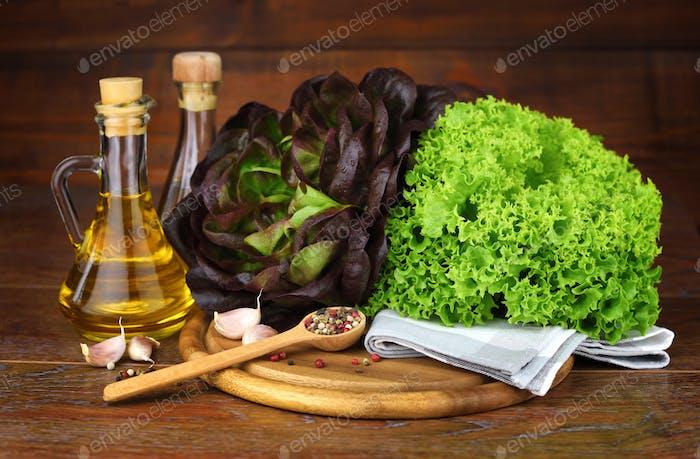 Fresh green and red lettuce, oil, seasonings on the wooden backg