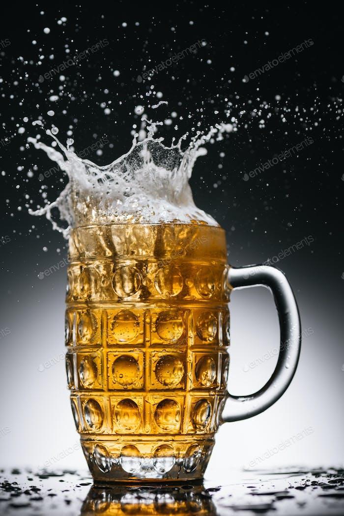 брызги холодного легкого спиртового пива в кружке