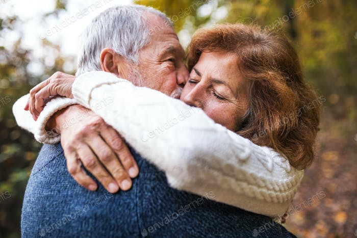 A close-up of a senior couple hugging in an autumn nature, kissing.
