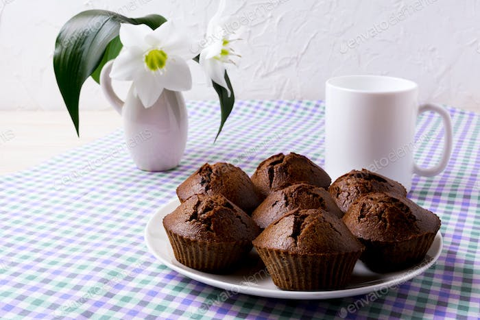 Chocolate muffins and coffee mug on the checkered napkin