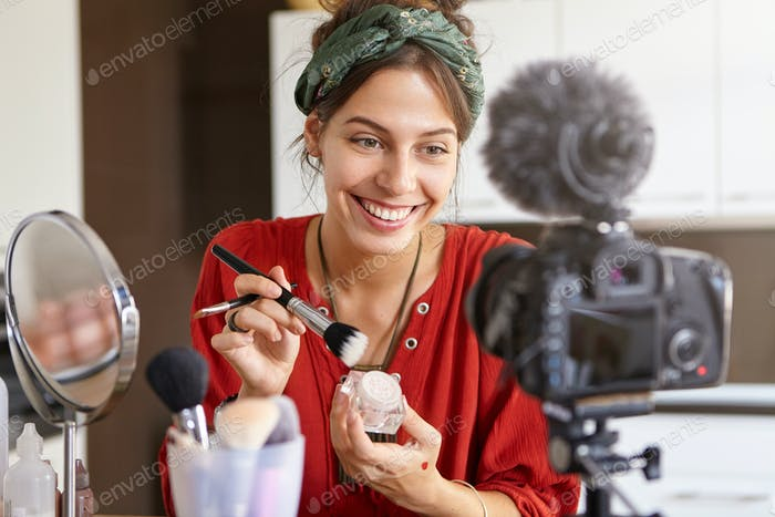 Cheerful teenage girl recording video tutorial at home, looking at camera fixed on tripod, sitting a