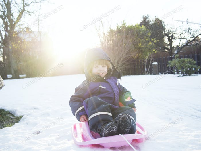 Happy girl sledding on snow covered field