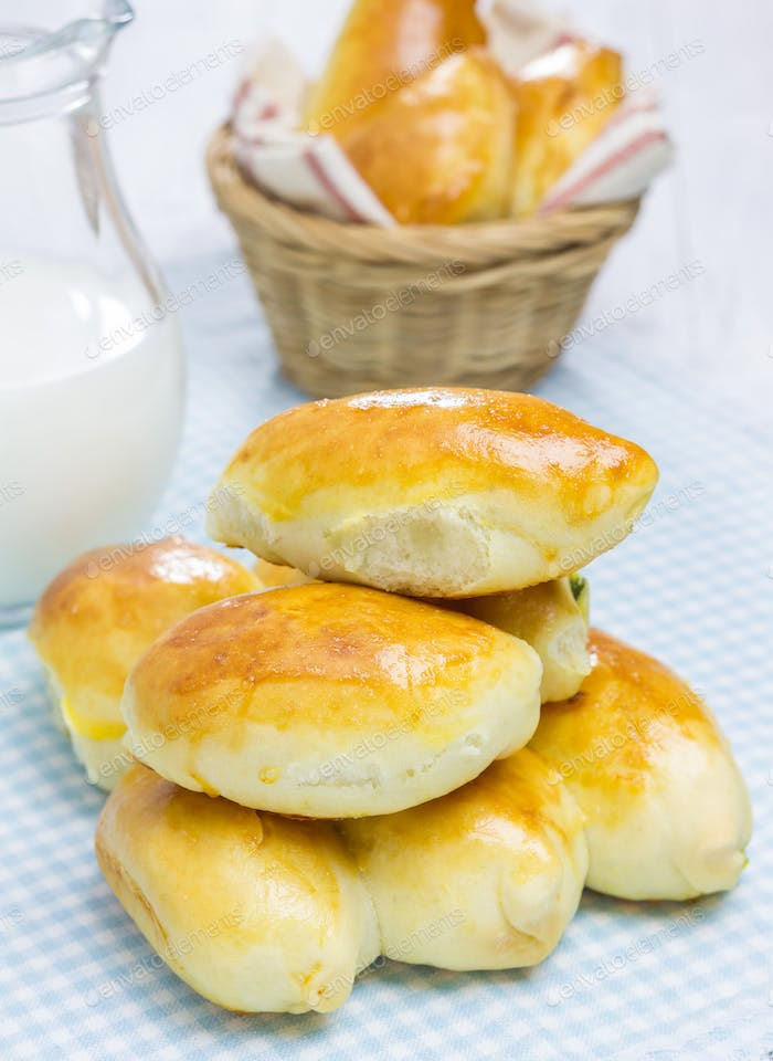 Russian pastries (pirogi) and milk on wooden table