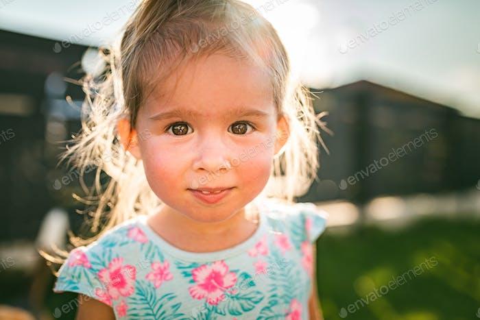 Красивый портрет девочки в солнечном, зеленом дворе летом