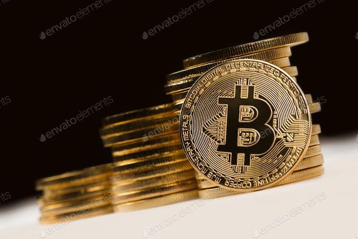 goldene Bitcoin vor einem Haufen goldener Metallic-Münzen auf bl