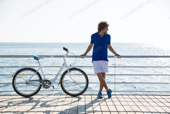 Handsome man with bicycle resting outdoors