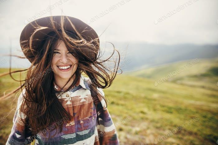 traveler hipster girl with windy hair and backpack, standing on top of sunny mountains