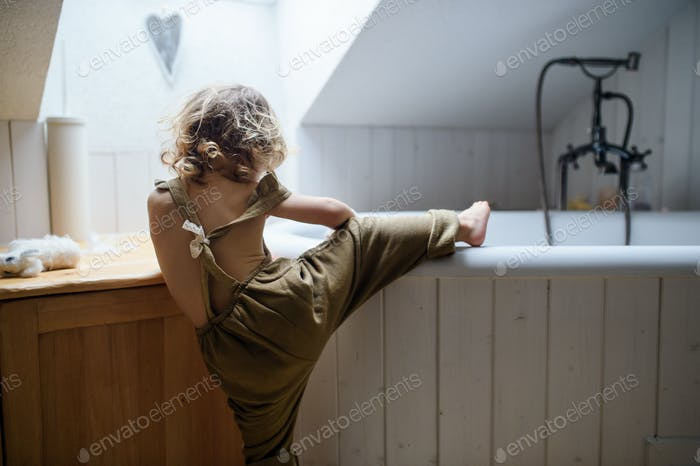 Rear view of small toddler child climbing into bath indoors at home