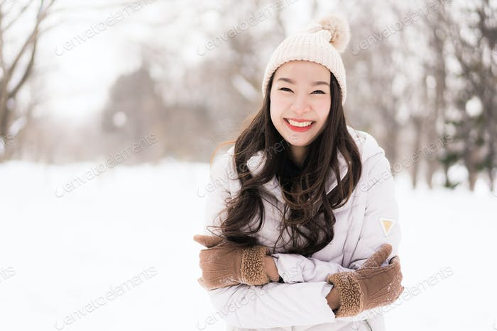 Beautiful young asian woman smiling happy for travel in snow win