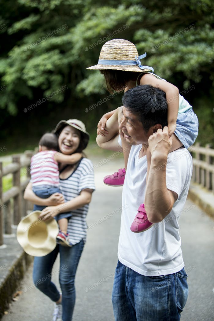 Family on a bridge, parents and children being carried.