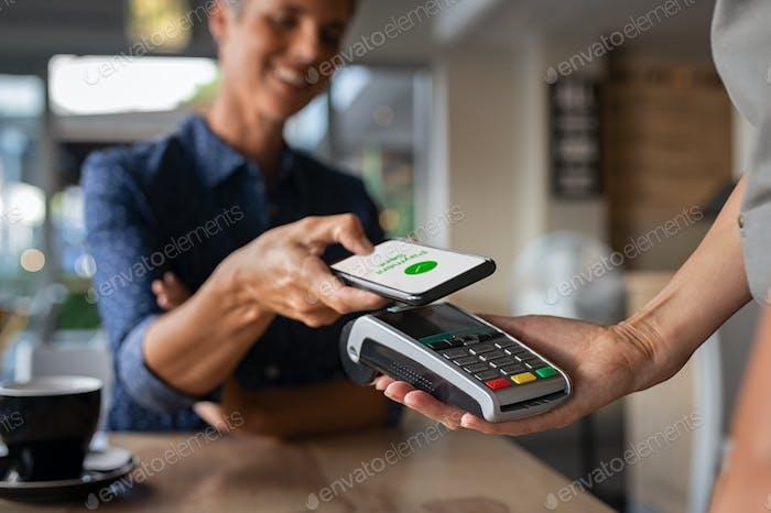 Frau zahlt mit NFC-Technologie