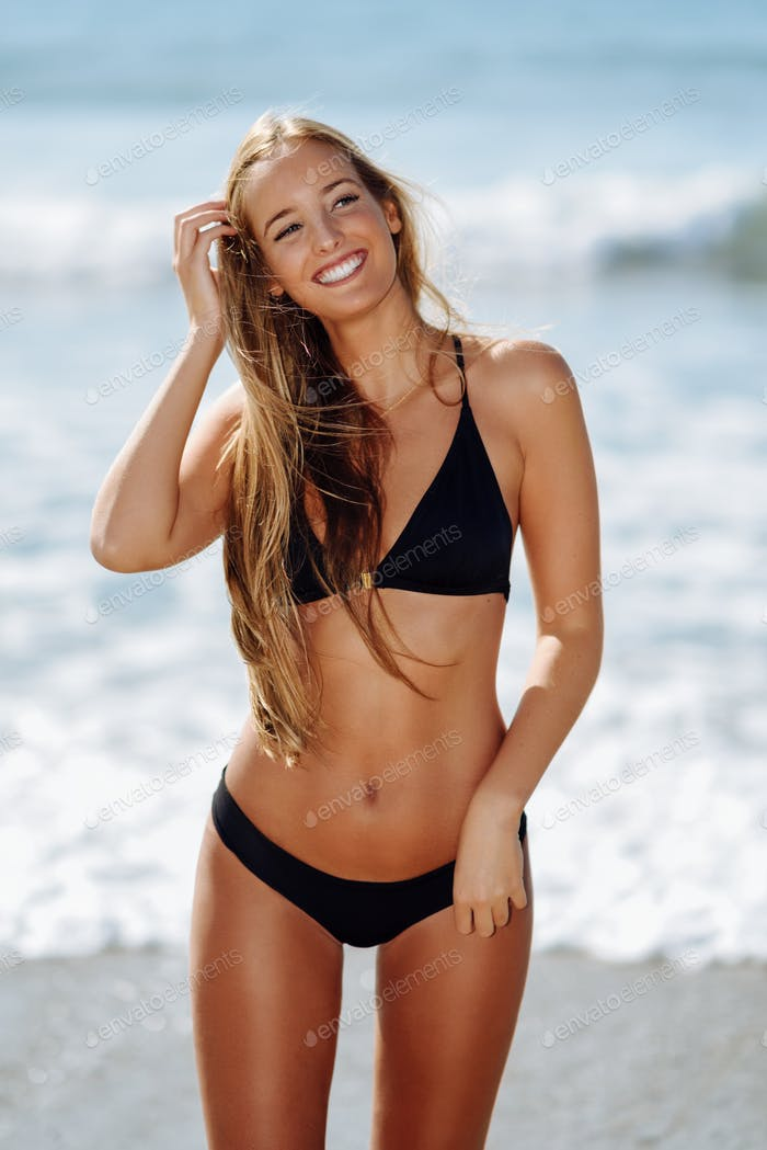 Young blonde woman with beautiful body in swimwear smiling on a