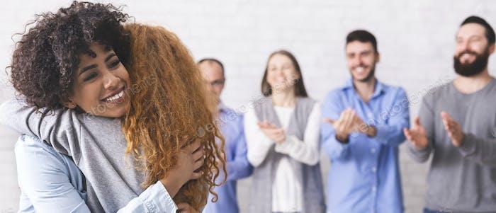 Fröhliche Menschen umarmen während der Gruppentherapie Sitzung