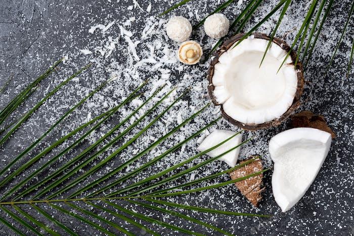 Draufsicht von frischer gebrochener Kokosnuss mit Spänen auf schwarz