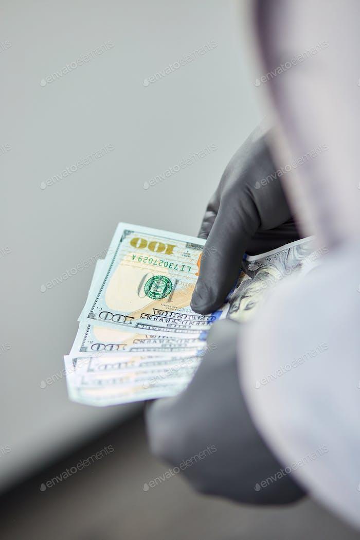 Hombre sosteniendo dólares de dinero en mano con guantes médicos negros.