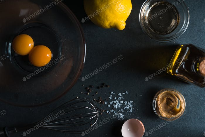Yolks in a bowl, whisk for whipping, mustard