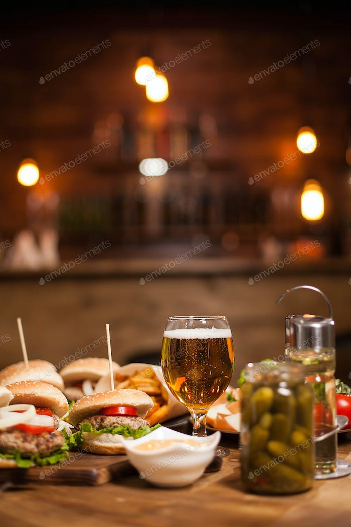 Mini burgers with a big glass of golden beer next to a jar of pickles