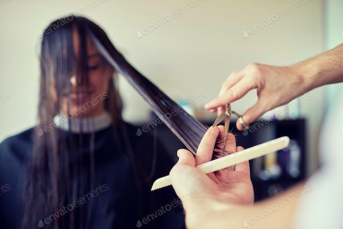 glückliche Frau mit Stylistin schneiden Haare im Salon