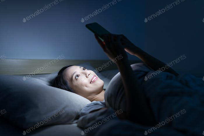 Woman using cellphone on bed at night