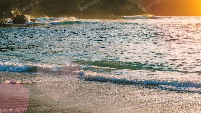 Lokale Kinder surfen auf Wellen in Sunset Light, Beautiful Crystal Bay, Nusa Penida Bali